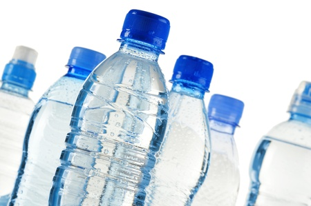 Composition with polycarbonate plastic bottles of mineral water isolated on white background photo