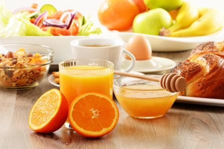 light breakfast: Breakfast including coffee, bread, honey, orange juice, muesli and fruits Stock Photo