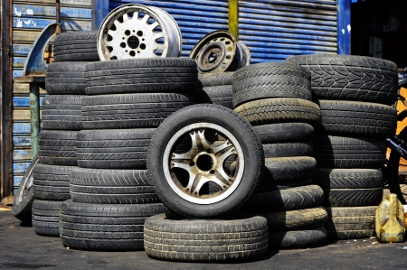 Stacks of old used tires in front of the auto service station photo