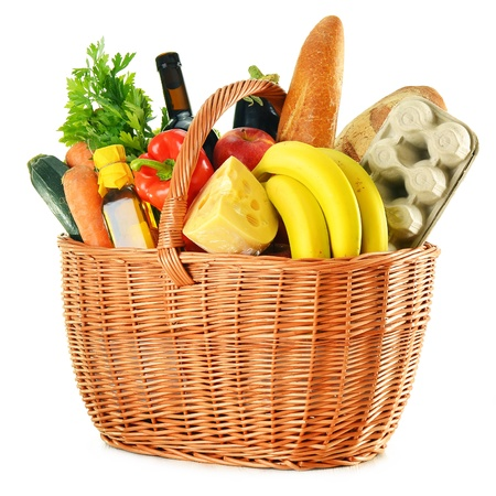 Wicker basket with variety of grocery products isolated on white