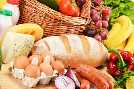 bread basket: Assorted grocery products including vegetables fruits wine bread dairy and meat Stock Photo