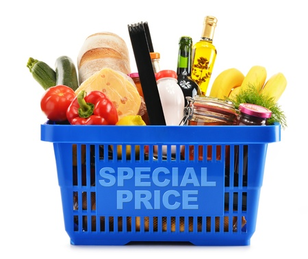 Plastic shopping basket with variety of grocery products isolated on white