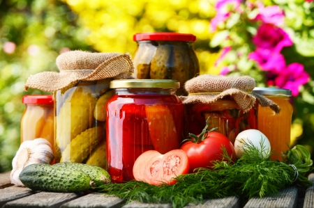Jars of pickled vegetables in the garden. Marinated food Banco de Imagens