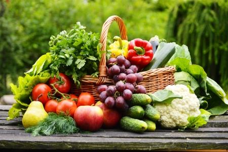 canastas con frutas: Vegetales orgánicos frescos en la cesta de mimbre en el jardín
