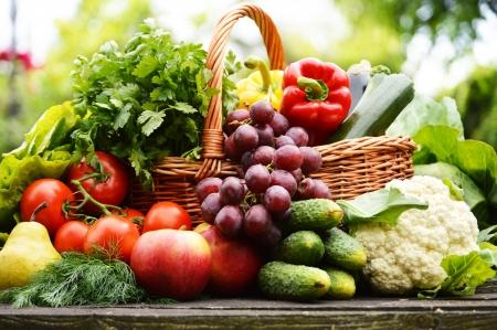 verduras verdes: Vegetales org?nicos frescos en la cesta de mimbre en el jard?n Foto de archivo