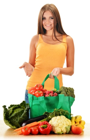 Young woman with variety of grocery products in shopping bag isolated on white photo