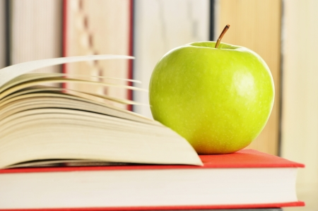 Composition with green apple and books on the table photo