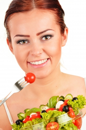 Young woman eating vegetable salad photo