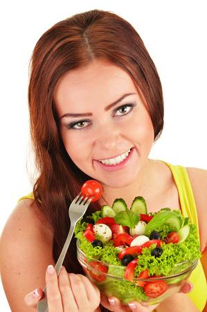 Young woman eating vegetable salad photo