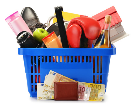 Variety of consumer products in plastic shopping basket isolated on white photo