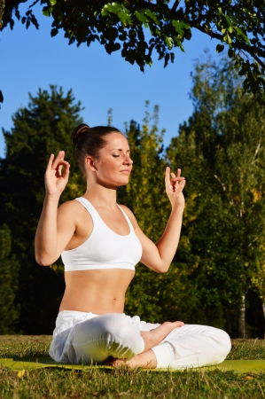 tree position: Young woman during yoga meditation in the park Stock Photo