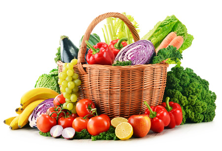 vegetable basket: Wicker basket with assorted organic vegetables and fruits  isolated on white