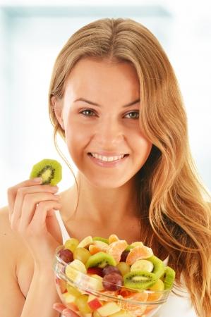 フルーツ サラダを食べる若い女性 写真素材