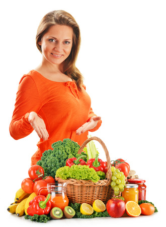 Young woman with variety of organic vegetables isolated on white  photo