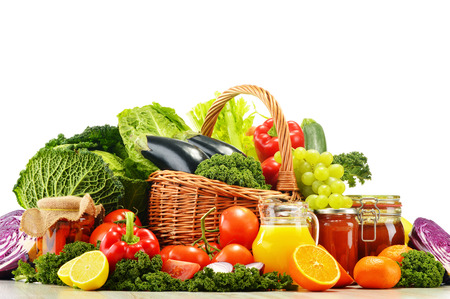 Wicker basket with assorted organic vegetables and fruits  isolated on white photo