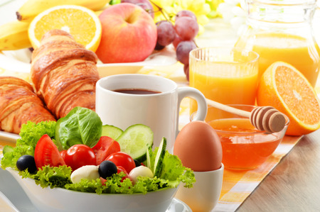 Breakfast with coffee, orange juice, croissant, egg, vegetables and fruits photo