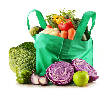 Shopping bag with variety of fresh organic vegetables isolated on white photo