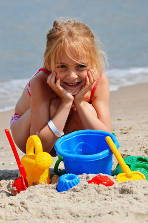 sand mold: Little girl playing on the sand beach  Stock Photo