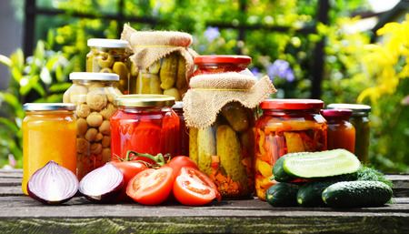 Jars of pickled vegetables in the garden  Marinated food  photo