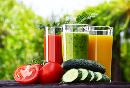 Glasses with fresh vegetable juices in the garden  Detox diet photo
