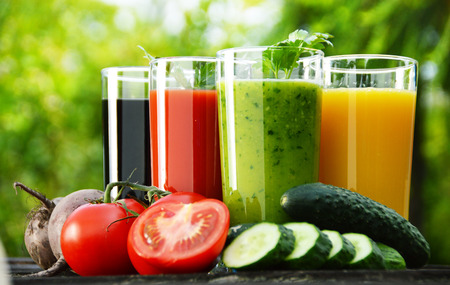 balanced diet: Glasses with fresh vegetable juices in the garden  Detox diet
