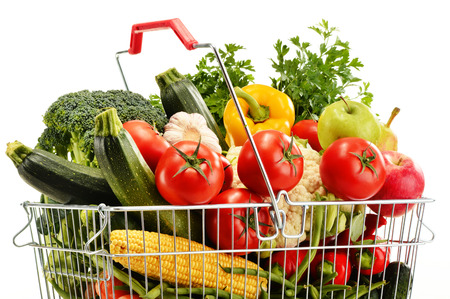 Wire shopping basket with groceries isolated on white background photo