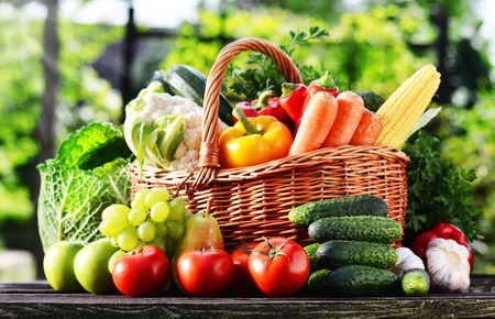 tomate de arbol: Cesta de mimbre con vegetales orgánicos crudos surtidos en el jardín. Foto de archivo