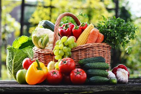 verduras verdes: Cesta de mimbre con vegetales org�nicos crudos surtidos en el jard�n. Foto de archivo