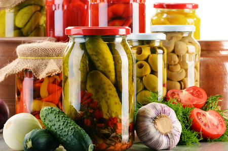 canned: Composition with jars of pickled vegetables. Marinated food.