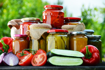 Jars of pickled vegetables in the garden. Marinated food. photo