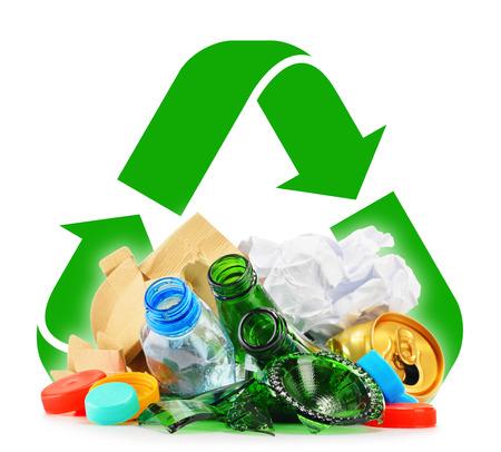 Composición con la basura reciclable que consiste en vidrio, plástico, metal y papel aislados sobre fondo blanco