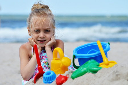 sand mold: Little girl playing on the sand beach.