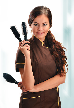 Professional hairdresser holding brushes photo