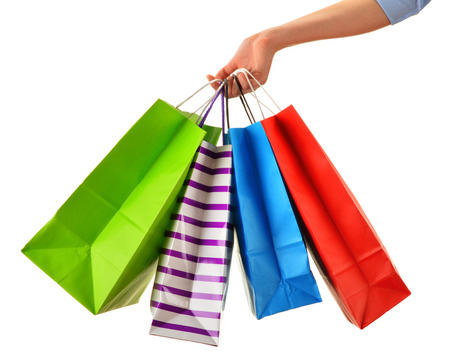 christmas shopping bag: Female hand holding paper shopping bags isolated on white background