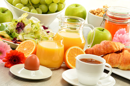 balanced diet: Breakfast consisting of fruits, orange juice, coffee, honey, bread and egg. Balanced diet