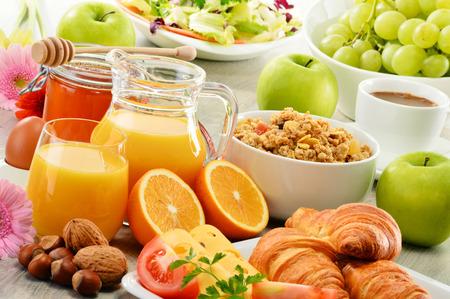 Petit-déjeuner composé de fruits, de jus d'orange, café, miel, pain et oeufs. Une alimentation équilibrée