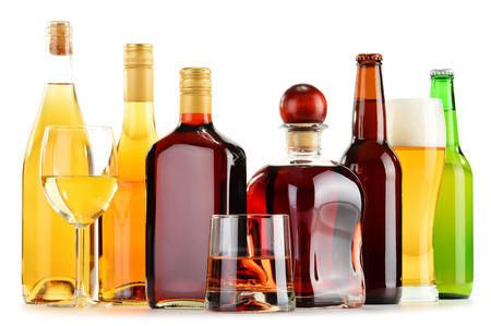 Bottles and glasses of assorted alcoholic beverages isolated on white background