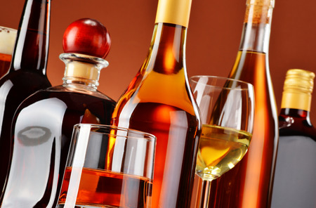 distilled alcohol: Bottles and glasses of assorted alcoholic beverages.
