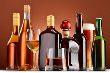 alcohol bottles: Bottles and glasses of assorted alcoholic beverages.