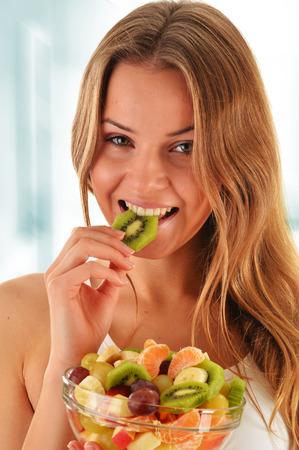 eating fruit: Joven mujer comiendo ensalada de frutas Foto de archivo