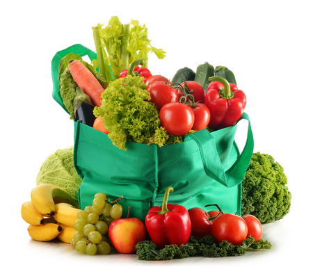 Green shopping bag with variety of fresh organic vegetables isolated on white photo