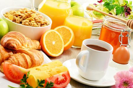 Breakfast consisting of fruits, orange juice, coffee, honey, bread and egg. Balanced diet photo
