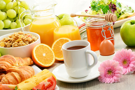 Breakfast consisting of fruits, orange juice, coffee, honey, bread and egg. Balanced diet