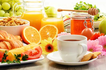 Breakfast consisting of fruits, orange juice, coffee, honey, bread and egg. Balanced diet