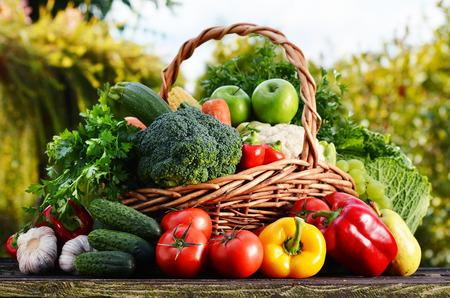 canastas con frutas: Cesta de mimbre con verduras orgánicas primas clasificadas en el jardín.