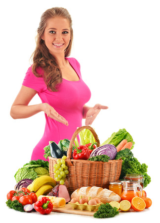 raw vegetables: Young woman with assorted grocery products isolated on white background