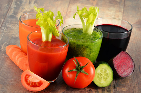 Glasses with fresh organic vegetable juices on wooden table. Detox diet photo