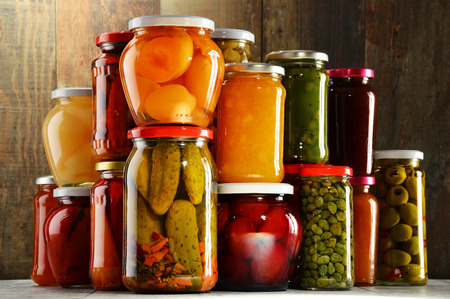 jams: Jars with pickled vegetables, fruity compotes and jams in cellar. Preserved food