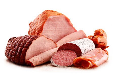 Assorted meat products including ham and sausages isolated on white Фото со стока
