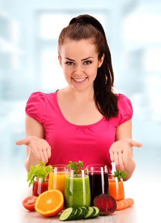 sano: Mujer joven con la variedad de jugos de frutas y verduras Foto de archivo